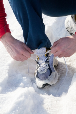 Clouse-up male runner tying jogging shoes before training photo