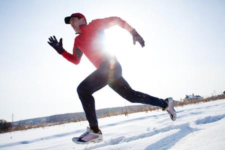 Athletic man fonctionne en journée d'hiver sur la neige Banque d'images