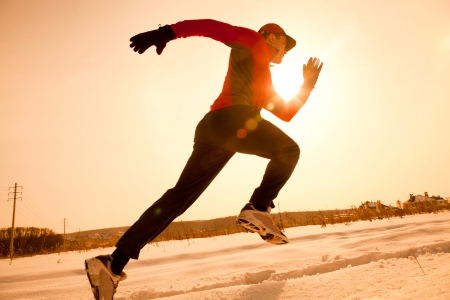 winter sunrise: Athletic  man running in winter morning Stock Photo