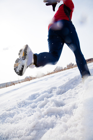 Athletic  man running in winter day. unrecognizable photo