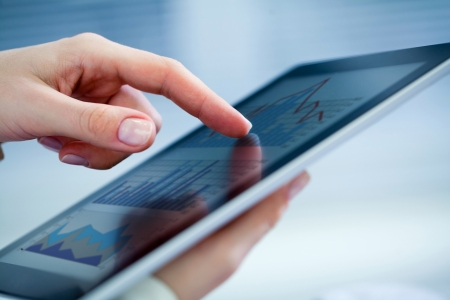 Gros plan sur les mains des femmes touchant tablette numérique avec le diagramme d'affaires