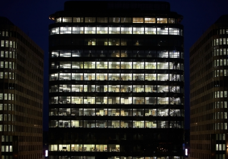 Business skyscraper of glass and steel office lighting and working people within
