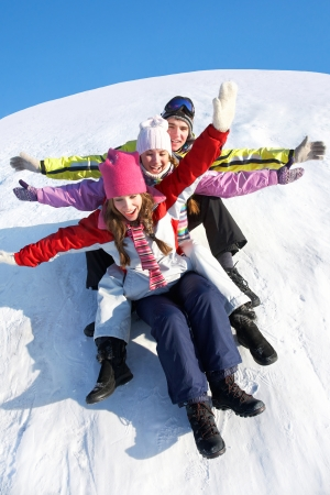 wintertime: Group of  teenagers slide downhill in wintertime Stock Photo