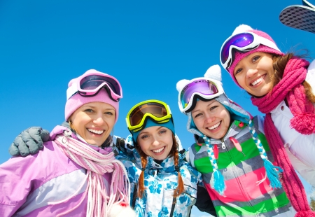 skis: Group of young woman on ski holiday in mountains  Stock Photo