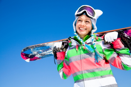 portrait of young smilling woman with snowboard on ski holiday in mountains