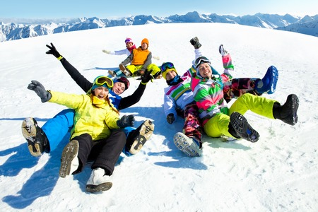 snow ski: group of funny friends slide downhill together on mountain holiday Stock Photo