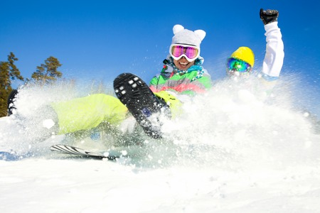 couple of young people  slide downhill together on mountain holiday