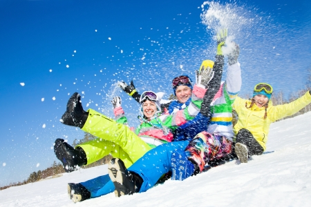 group of funny friends slide downhill together on mountain holiday Zdjęcie Seryjne