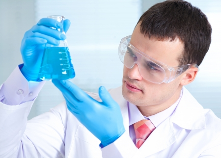 drug test: man scientist holding a test tube with liquid