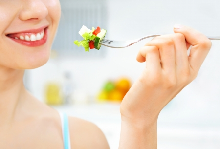 1 young woman only: close-up of woman eating fresh salad