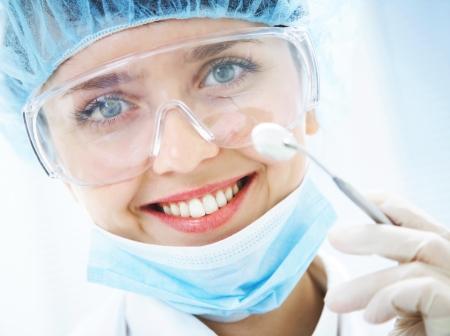 Portrait de dentiste sourire positive avec miroir dentaire