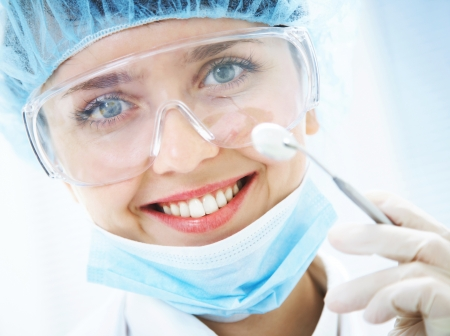 Portrait of positive smiling dentist with dental mirror photo