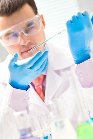 biochemist: Investigator checking test tubes. Man wears protective goggles Stock Photo