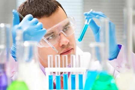 液で試験管を保持している人の科学者