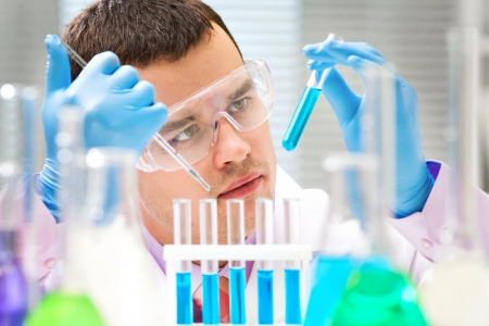 drug discovery: man scientist holding a test tube with liquid