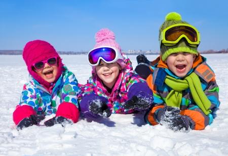 Groupe d'enfants jouant sur la neige en hiver Banque d'images