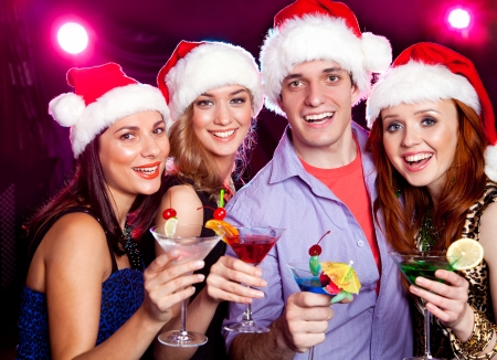 young friends dressed as Santa Claus with a cocktail in hand photo