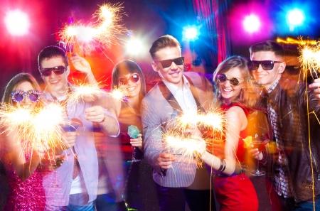 jeune entreprise célèbre la fête avec feux d'artifice dans les mains