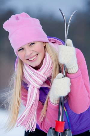 Portrait of blondy young woman with ski in winter time photo