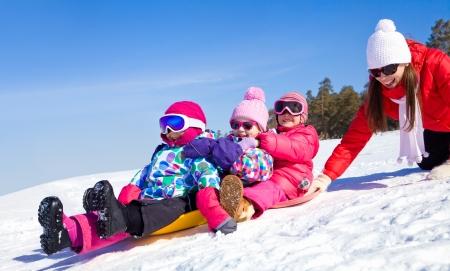 冬時間で雪に乗って子供を持つ若い母親のスライドします。 写真素材