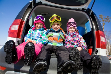 group of kids in winter clothes sitting in the trunk of a car Standard-Bild