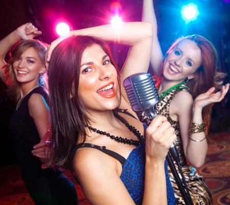 Jeune fille chantant dans le microphone à la fête