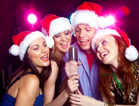 young friends in the bell Santa Claus sing karaoke microphone photo