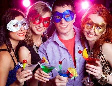 マスクの若い会社祝う休日カクテルを手に
