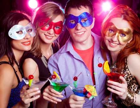 new year dance: young company in mask celebrates holiday with a cocktail in hand Stock Photo