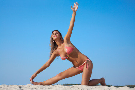 Mature sexy woman practicing yoga by the beach photo