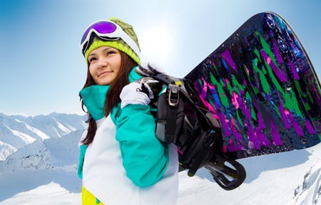 ski mask: young woman with a snowboard on a background of mountains Stock Photo
