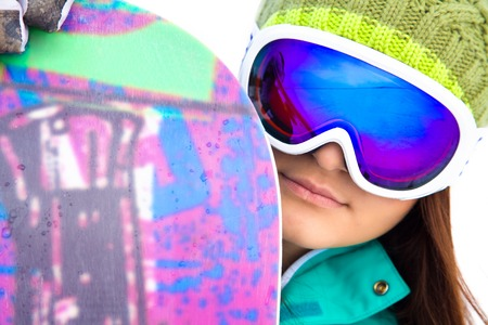 young woman in sport sunglasses with a snowboard  close-up photo