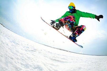 snowboarder jumping: snowboarder jumping from the mountaint along the road extreme Stock Photo