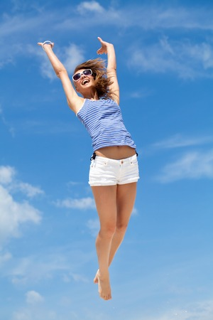 Jeune femme de bonheur saute contre le ciel bleu Banque d'images - 26659943