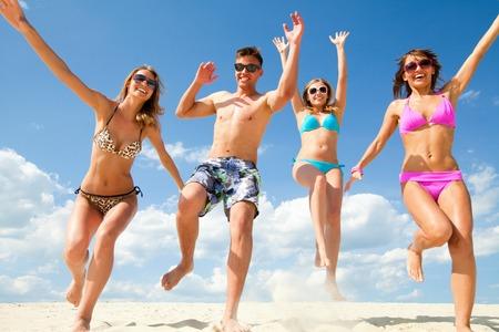 Young fun people enjoying summer on the beach photo