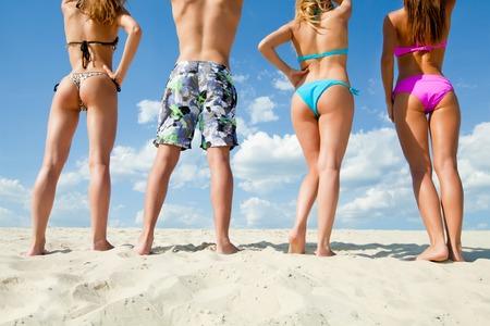 Mladí lidé mají dobrý čas na pláži Pohled zezadu k nepoznání