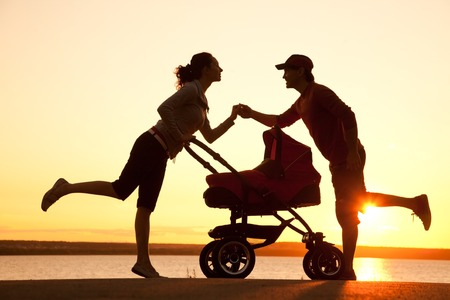 Silhouettes of parents loving  their child in a stroller Stock Photo - 27438768