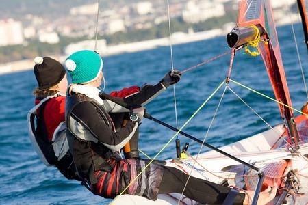yacht race: Personas de dos chicas h�bilmente logr� navegar en el mar Foto de archivo