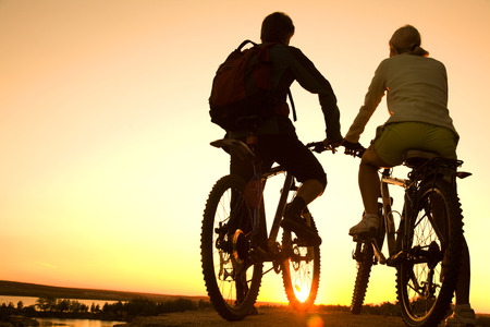 brink: Couple of bicyclists on the brink of  rock looks at  sunset