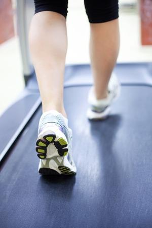 womans muscular legs on treadmill, closeup photo