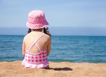 little girl sitting on the beach and sunbathe in the sun photo
