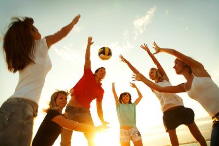 játék: csoport fiatal játszik röplabda a strandon Stock fotó