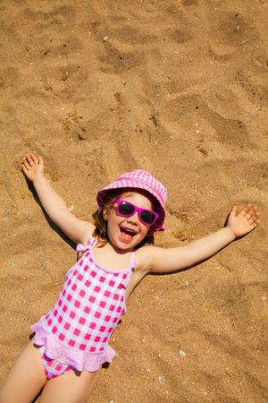 girl in a hat: little girl lying on a sandy beach and sunbathe in the sun