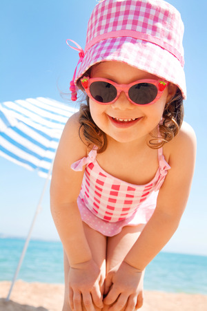little girl smiling fun in the hot beach under an umbrella