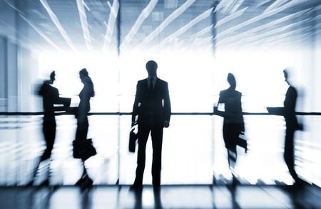 Several  silhouettes of businesspeople interacting  background business centre Stockfoto