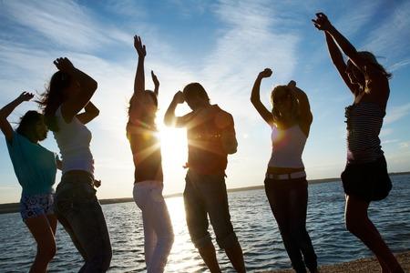 juventud: Grupo de jóvenes felices bailando en la playa en el atardecer de verano hermosa