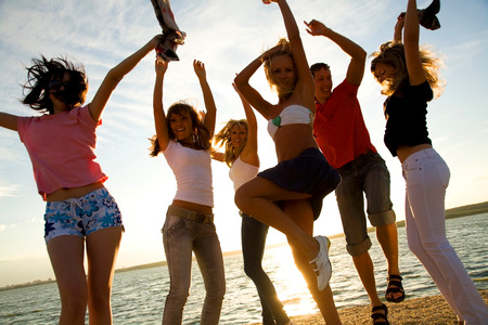 happy young people: group of happy young people dancing at the beach on  beautiful summer sunset