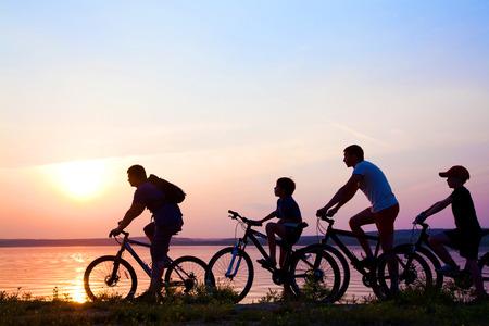 silueta ciclista: de la familia en bicicleta admirando la puesta de sol en el lago. silueta