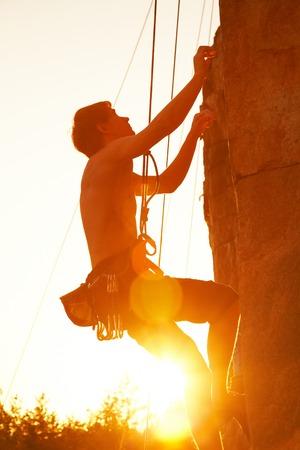 climbing: Siluetas del hombre de escalada en un acantilado al atardecer