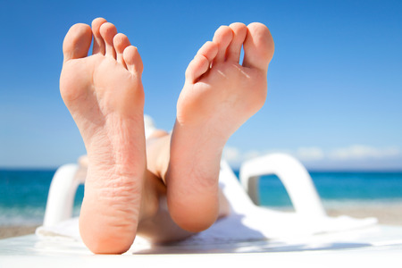 Young woman relaxing in chaise longue on the beach Stock Photo - 27439678